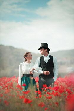Ildiko Neer Historical couple walking in poppy field