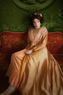 ILINA SIMEONOVA WOMAN IN ORANGE SILK SITTING IN ORNATE INTERIOR