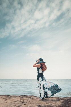 Evelina Kremsdorf WOMAN HOLDING HAT ON BREEZY BEACH