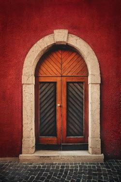 Evelina Kremsdorf ARCHED WOODEN DOOR IN RED BUILDING
