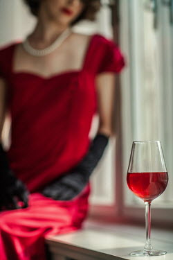 Nikaa WOMAN IN RED BY WINDOW WITH GLASS OF WINE
