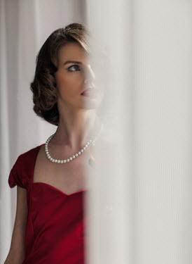 Nikaa BRUNETTE WOMAN IN RED BY WINDOW