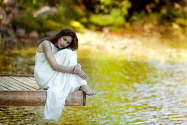 Marina Chebanova WOMAN IN WHITE SITTING ON JETTY BY WATER