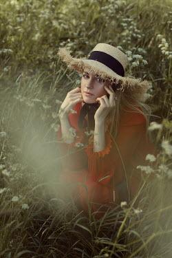 Marina Chebanova BLONDE WOMAN WITH STRAW HAT CROUCHING IN MEADOW