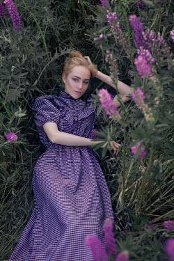 Marina Chebanova WOMAN IN PURPLE DRESS LYING WITH FLOWERS