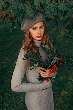 Marina Chebanova WOMAN IN BERET STANDING BY TREE WITH RED BERRIES