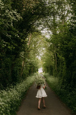 Rebecca Stice GIRL CARRYING FLOWERS ON COUNTRY LANE