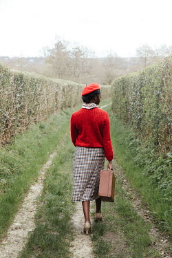 Matilda Delves BLACK WOMAN CARRYING SUITCASE IN COUNTRY LANE