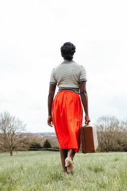 Matilda Delves BLACK WOMAN CARRYING SUITCASE IN COUNTRYSIDE