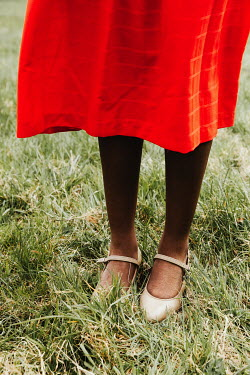 Matilda Delves LEGS AND FEET OF WOMAN WITH RED SKIRT OUTDOORS