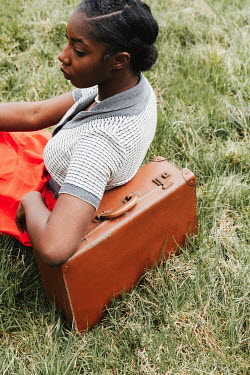 Matilda Delves BLACK RETRO WOMAN SITTING WITH SUITCASE IN FIELD