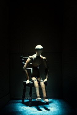 Magdalena Russocka posable wooden mannequin sitting on miniature chair in shadow