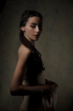 Daniel Murtagh GIRL WITH LONG DARK HAIR STANDING IN SHADOW