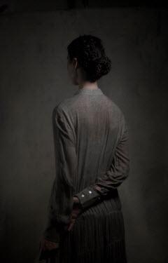 Daniel Murtagh GIRL WITH PLAITED DARK HAIR STANDING IN SHADOW