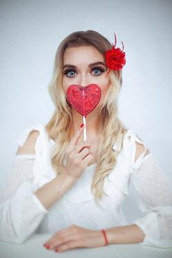 Marina Chebanova BLONDE WOMAN HOLDING RED HEART-SHAPED LOLLIPOP