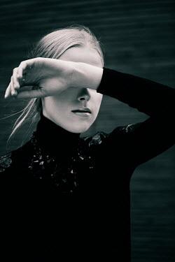 Marina Chebanova BLONDE WOMAN COVERING FACE WITH HAND OUTDOORS