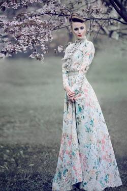 Marina Chebanova WOMAN IN LONG FLORAL DRESS BY TREE IN BLOSSOM