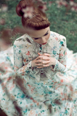 Marina Chebanova WOMAN IN FLORAL DRESS SITTING ON GRASS