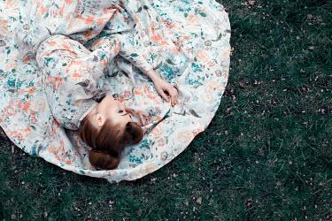 Marina Chebanova WOMAN IN FLORAL DRESS LYING ON GRASS