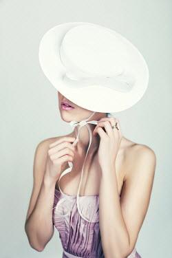 Marina Chebanova WOMAN IN PINK DRESS TYING RIBBONS OF WHITE HAT