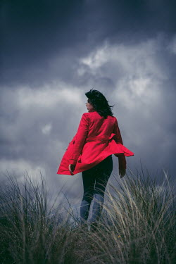 Marie Carr WOMAN IN RED COAT WALKING ON WINDY DUNES
