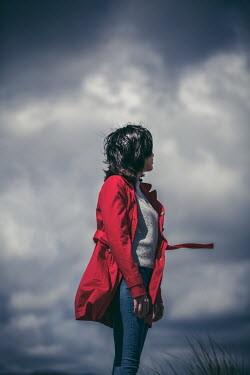 Marie Carr WOMAN IN RED COAT OUTDOORS WITH STORMY SKY