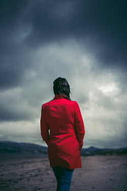 Marie Carr WOMAN IN RED COAT WALKING ON BEACH