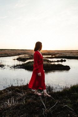 Matilda Delves WOMAN IN RED WALKING IN MARSHLAND AT DUSK