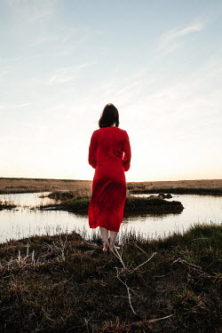 Matilda Delves WOMAN IN RED STANDING IN MARSHLAND AT DUSK