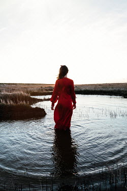 Matilda Delves WOMAN IN RED STANDING IN RIVER AT SUNSET