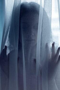 Ebru Sidar WOMAN WITH DARK HAIR BEHIND WHITE CURTAIN