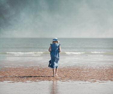 Anna Buczek LITTLE GIRL IN HAT ON SANDY BEACH