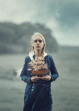 Anna Buczek BLONDE GIRL HOLDING MODEL SHIP ON BEACH