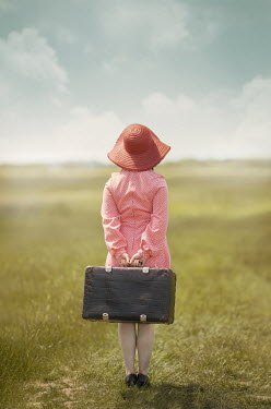 Anna Buczek GIRL WITH HAT HOLDING SUITCASE IN FIELD
