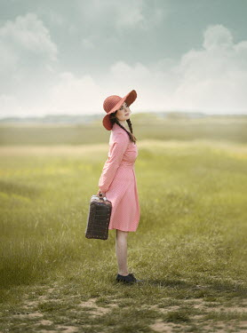 Anna Buczek GIRL WITH HAT CARRYING SUITCASE IN FIELD