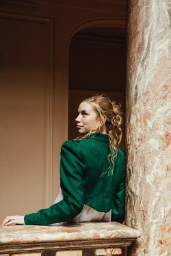 Matilda Delves BLONDE HISTORICAL WOMAN BY MARBLE PILLAR INDOORS
