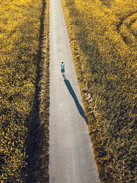 Magdalena Russocka retro woman with suitcase standing on country road from above