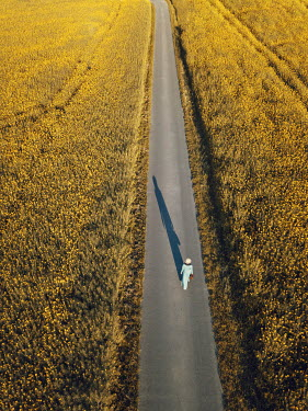Magdalena Russocka retro woman with suitcase walking on country road from above
