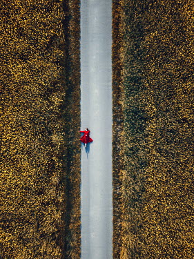 Magdalena Russocka woman in red dress lying on country road from above