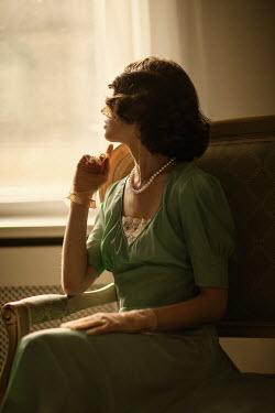 Nikaa RETRO BRUNETTE WOMAN SITTING INDOORS BY WINDOW