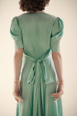 Nikaa BRUNETTE RETRO WOMAN IN GREEN DRESS WITH GLOVES