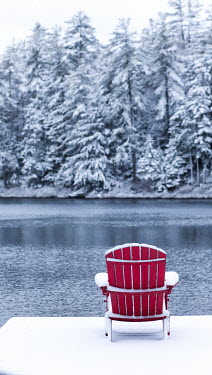 Jean Ladzinski RED CHAIR IN SNOW BY LAKE WITH TREES