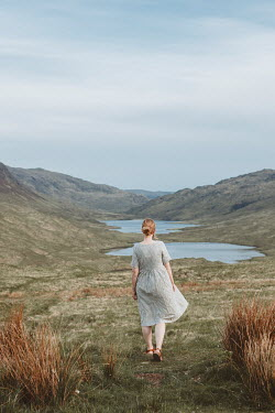 Shelley Richmond WOMAN IN DRESS WALKING IN LANDSCAPE WITH LAKES