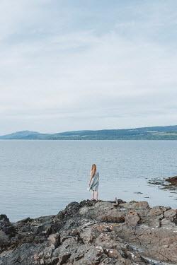 Shelley Richmond GIRL STANDING ON ROCKS WATCHING SEA