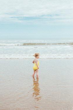 Shelley Richmond LITTLE BLONDE GIRL PADDLING IN SEA