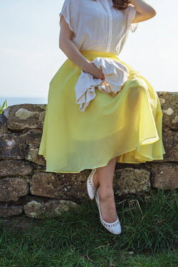 Marie Carr WOMAN IN YELLOW SKIRT SITTING ON COASTAL WALL