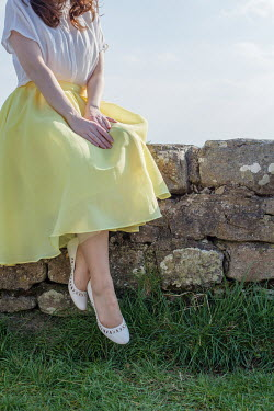 Marie Carr WOMAN IN YELLOW SKIRT SITTING ON WALL