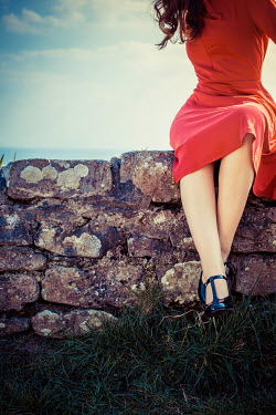 Marie Carr BRUNETTE WOMAN IN RED DRESS SITTING ON COASTAL WALL