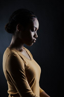 Magdalena Russocka young african woman wearing yellow jumper  in shadow inside