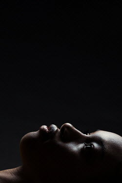 Magdalena Russocka close up of young african woman lying in shadow inside